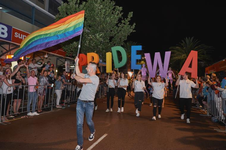People walk down a street holding a rainbow flag and the letters PRIDE WA