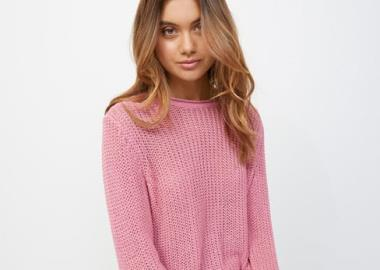Girl wearing a knitted pink jumper.