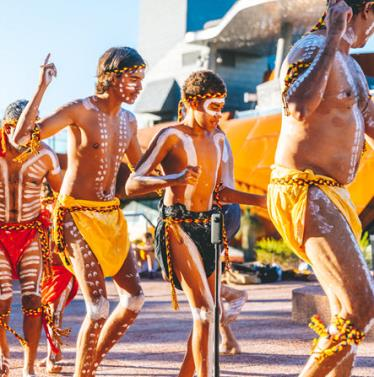 Aboriginal children and adults dance wearing coloured outfits