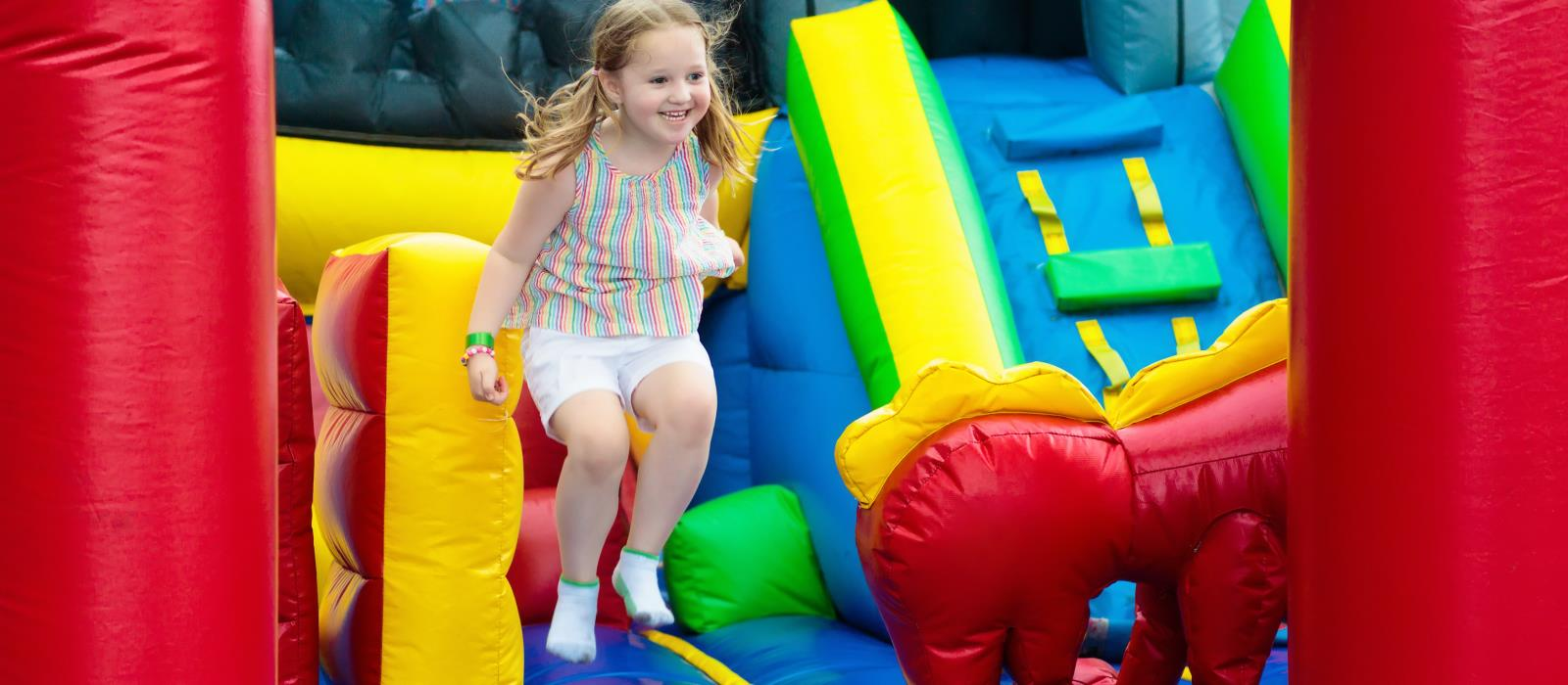 Young girl jumping on bouncy castle