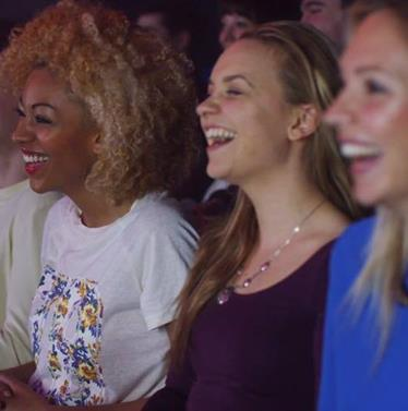 Women laughing at a comedy event