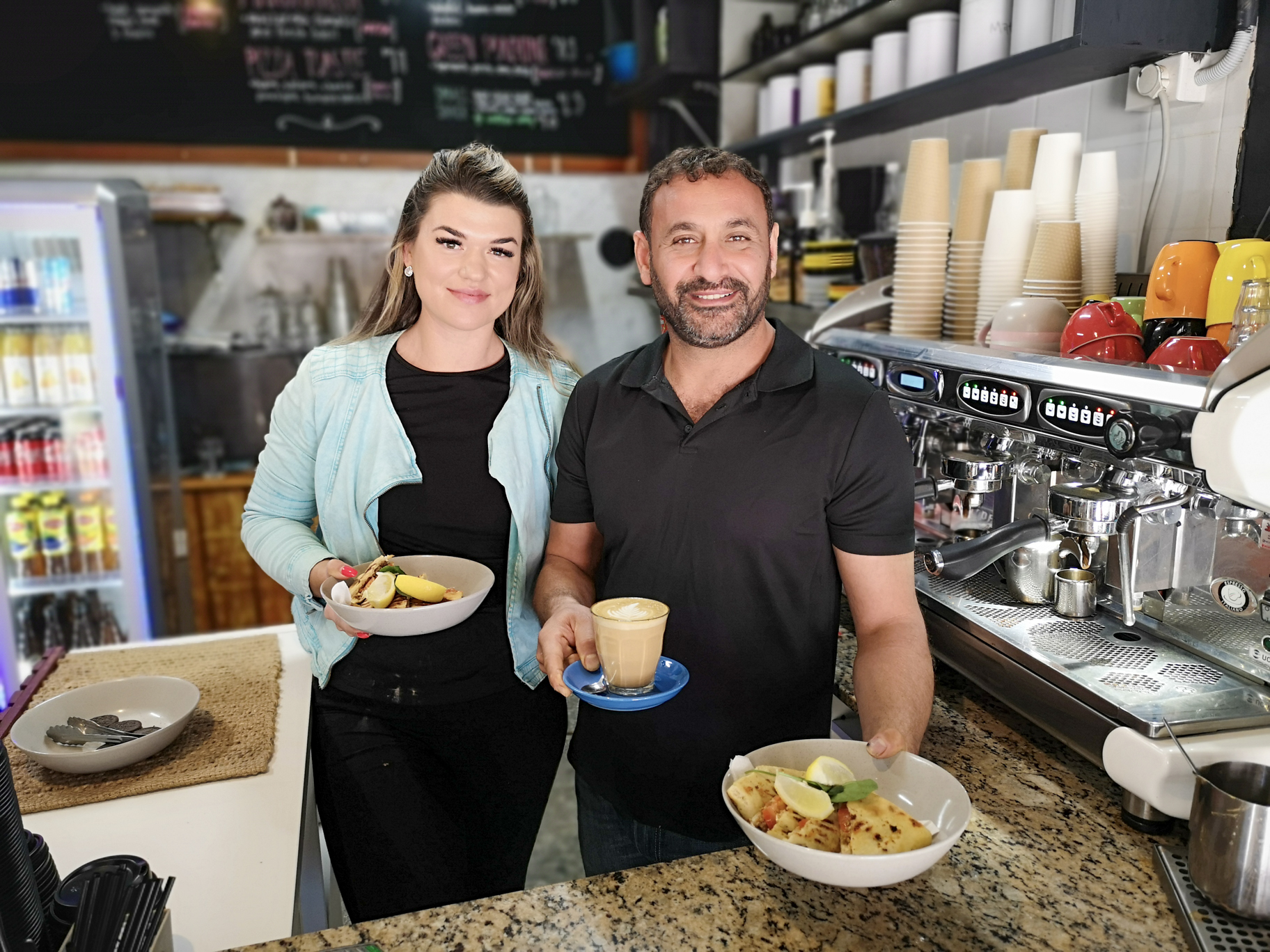Lady and man holding plates of food in a cafe